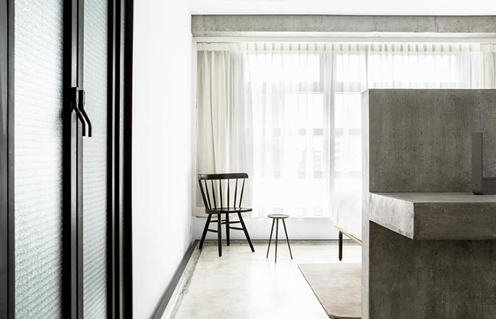 TUVE Boutique Hotel room interior, a glass door, a small concrete wall, and a chair in front of the window.