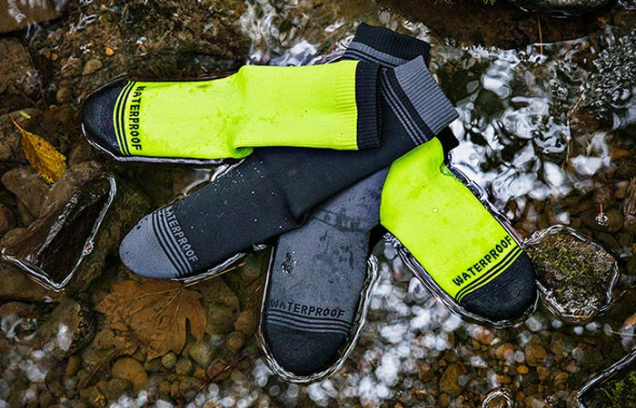 Showers Pass Waterproof Crew Socks, black/grey and neon yellow, lying on some rocks in a stream.