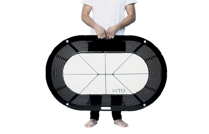 XTEND Portable Bathtub, packed for transportation, a figure of a man holding it in front of his body. White background.