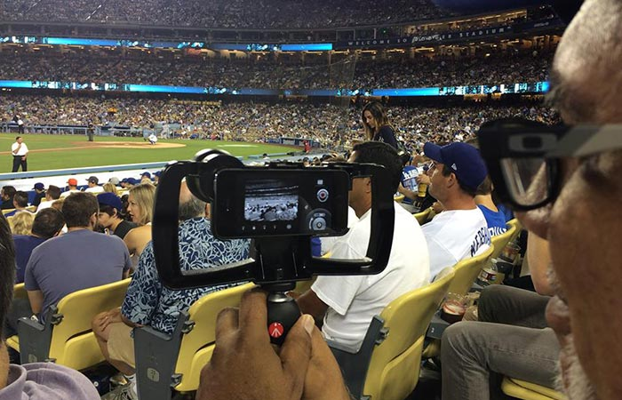 A man filming the NFL game captured from behind.
