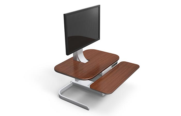 Crossover Motorized Standing Desk , brown with aluminum frame, tilted, with a computer monitor on top, on a white background.