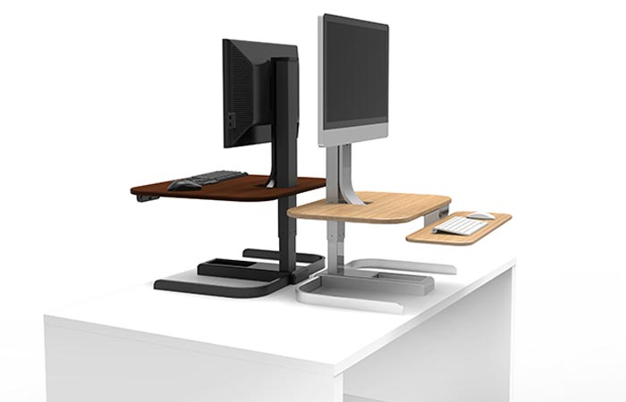 Crossover Motorized Standing Desks, brown and tan, on a white deck, with monitors on it, facing opposite directions, on a white background.