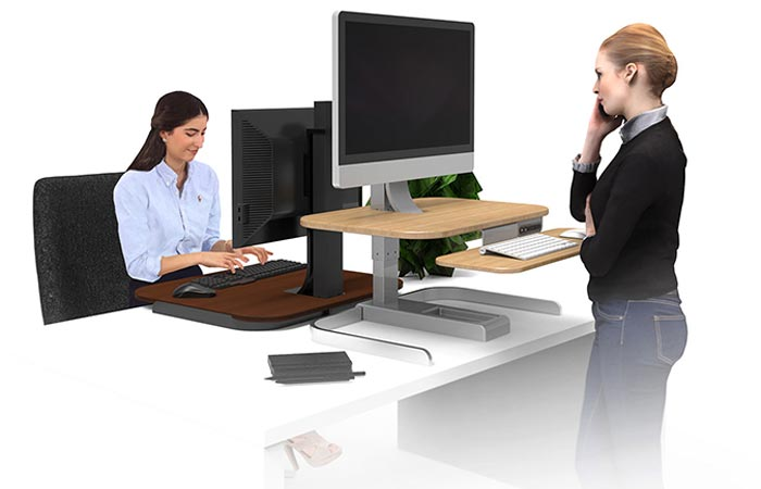 Two women working on computers placed on Crossover Motorized Standing Desks, sitting down and standing up, facing each other.