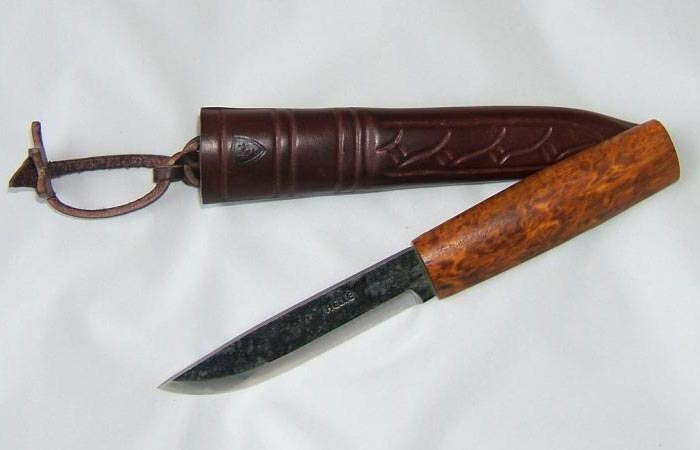 Helle Viking Knife with the protective leather sheath, on a white sheet.