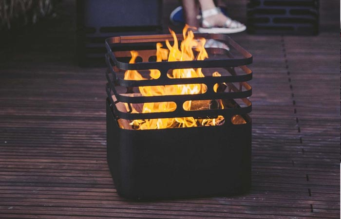 Höfats CUBE Fire Pit, with fire burning inside, on a wooden floor with a person's feet in the background.