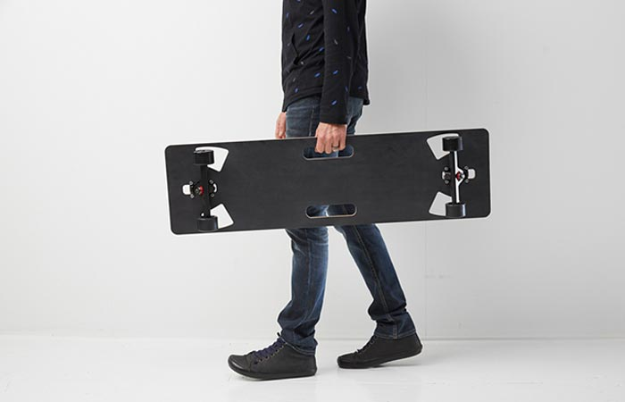 A man carrying the Lo-Ruiter Longboard, side view, in front of a white wall.