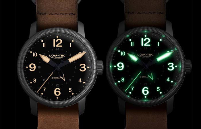Lum Tec Combat B33 GMT watch with brown leather strap and white display and with black nylon strap and old radium tone luminescence, on a black background.