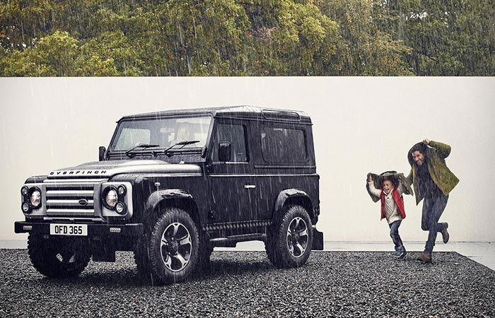 Defender captured from the distance alongside with some people on the rain.