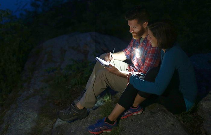 A man and a woman reading something in the dark and using the gadget.