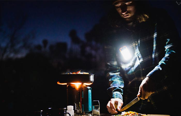 A guy camping and using the gadget during the night.