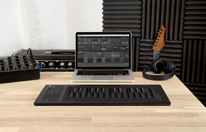 Roli Seaboard Rise on a wooden table with a laptop and headphones and a guitar and music production equipment in the background.