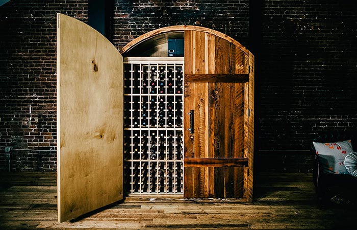 Sommi WIne Cellar in front of a brick wall, semi-open.