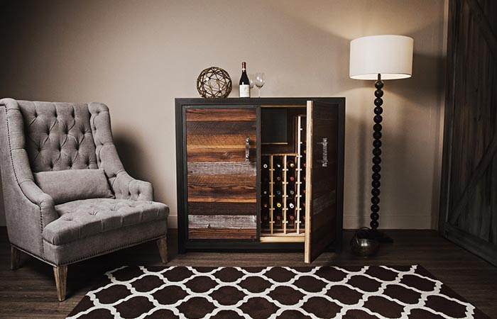 Sommi Credenza WIne Cellar with an armchais on the left and a lamp on the right, in front of a wall, semi-open, front view.