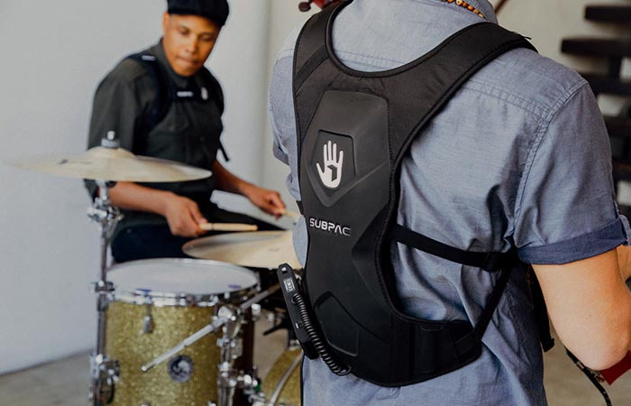 SubPac M2 worn by a man in a grey tee shirt, back view, tilted, and a man behind the drums.