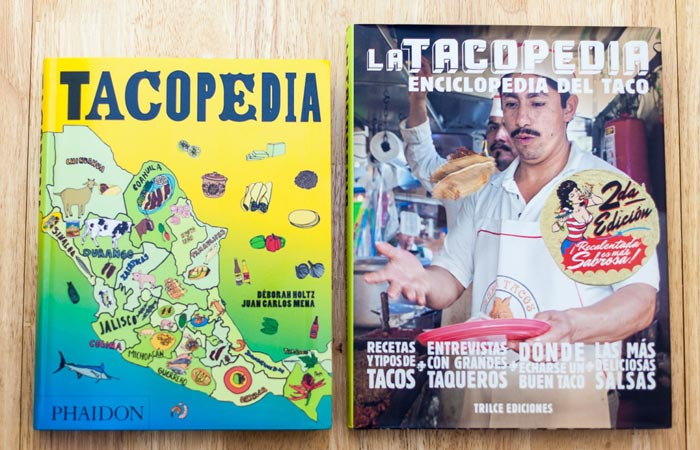 Tacopedia, adapted English version and original Mexican edition, on a wooden surface.
