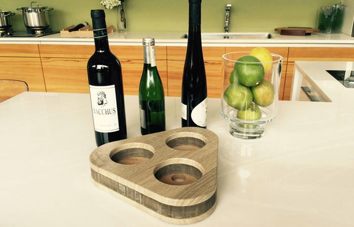 The Deck - Flexible Wine Holder, folded, on the kitchen counter with three different wine bottles and with a bowl of apples.