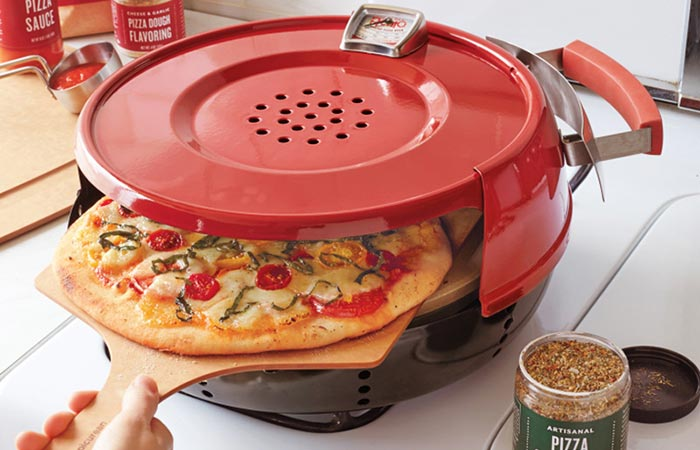Pizzacraft Stovetop Pizza Oven on a gas stove with a pizza on a wooden pizza peal halfway in.