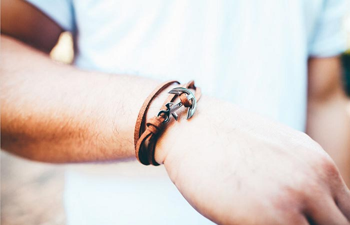 Thread Etiquette Chestnut Leather Anchor Bracelet on the hand of a man in white tee shirt.