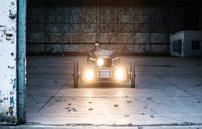 A Guy Driving Morgan EV3 Electric Car With The Lights Turned On