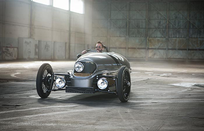 A Guy Driving Morgan EV3 Electric Car In The Empty Hall
