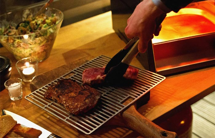 Steak that has been cooked on one side with Otto's over-fired broiler