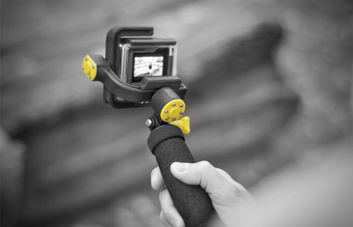Black And White Image Of A Hand Holding STABYLIZR GoPro Camera Stabilizer