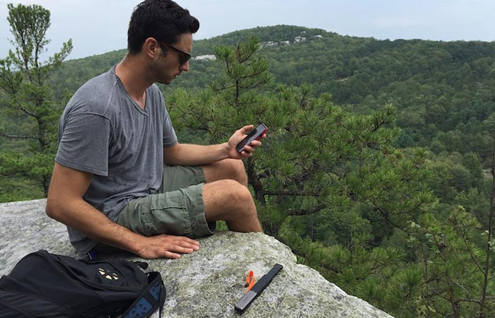 goTenna on a rock next to a guy while he's using his phone.