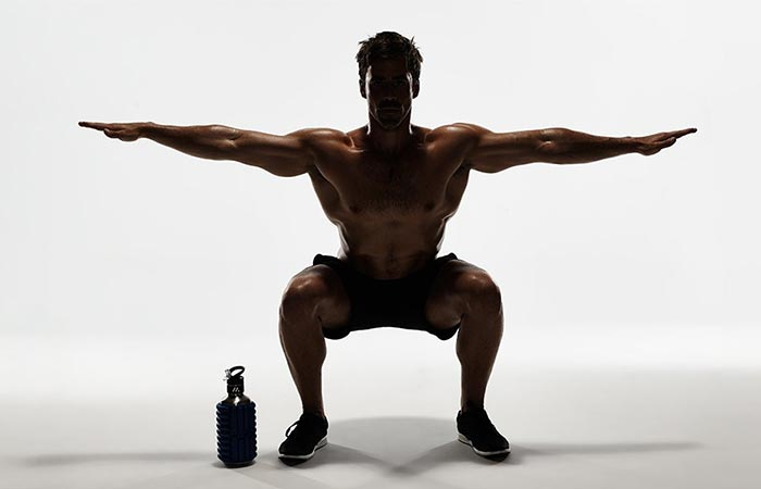 A Guy Excercising With Mobot Water Bottle & Roller Next To Him