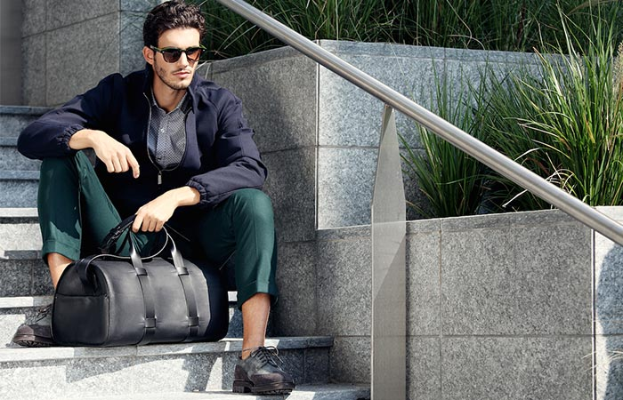 A Guy Sitting On A Staicase With A Troubadour Day Bag