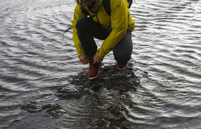 Man tying his shoe laces while standing in water