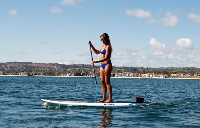 Woman using the Bixpy Swim Jet on her paddle board