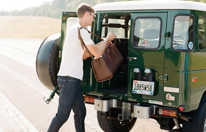 Man putting the Leon Weekender into his jeep.