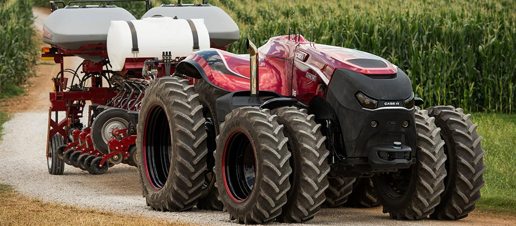 Side view of the Cabless Case IH pulling a cart in a corn field