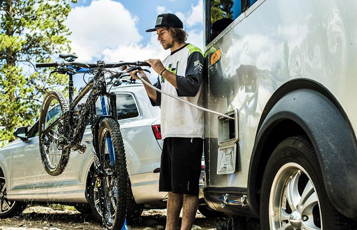 A Guy ashing A Bike In Front Of Airstream Basecamp