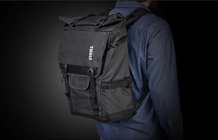 A Guy Wearing Thule Covert DSLR Rolltop Backpack