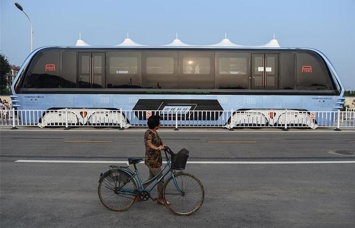 World's First Transit Elevated Bus side view with a woman walking with her bicycle
