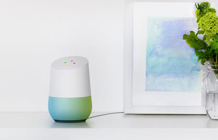 Google Home On A White Table Next To A Painting