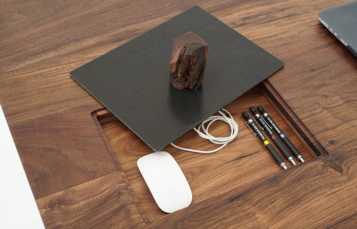 a mouse pad and a small opening in the desk