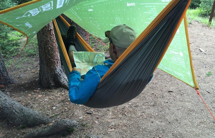 Man using The Original Trip Tarp as a hammock cover