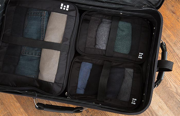 a suitcase with three compression bags inside