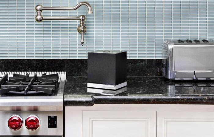 small black cube speaker on the kitchen counter
