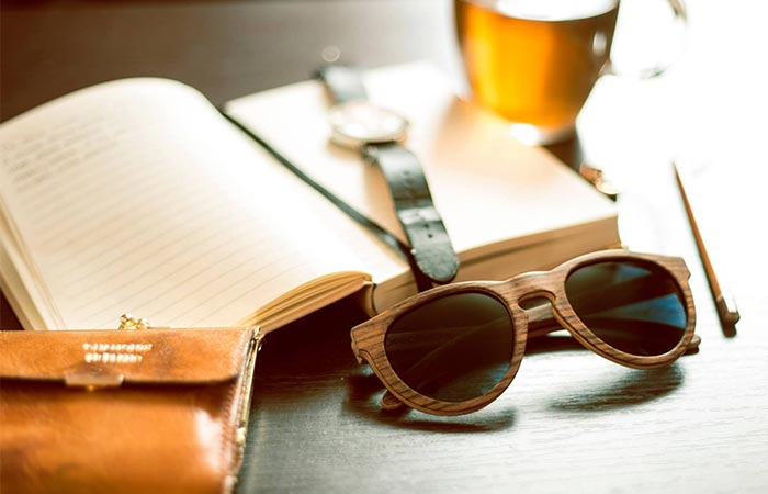 wooden glasses next to a book, watch and beer glass