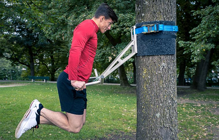 Man using the Pullup & Dip outside on a tree