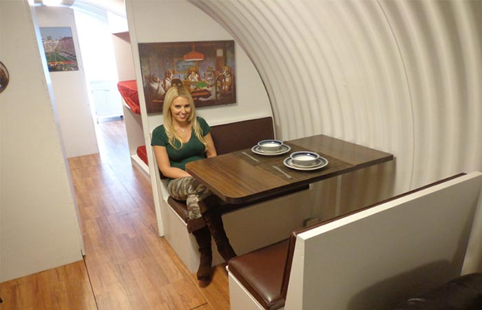 Girl sitting at a dining room table inside an Atlas Survival Shelter
