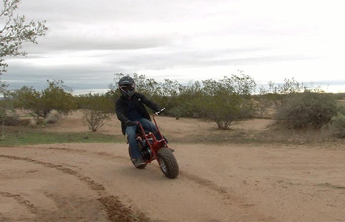 Man using the Coleman Powersports Mini Trail Bike