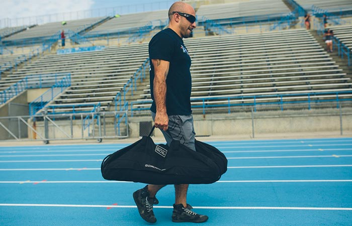 Man carrying twin GoRuck 60lb Training Sandbags