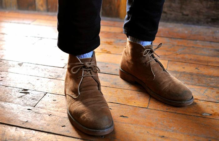 standing on wooden floor in brown chukka boots