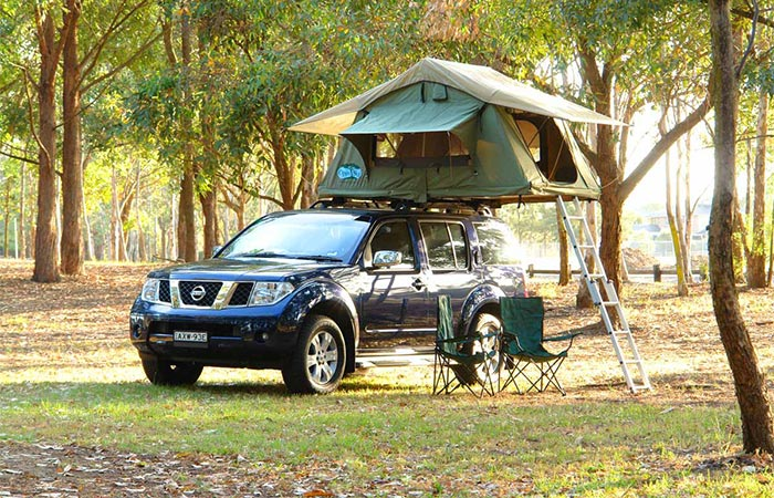 a nissan car with a rooftop tent on it