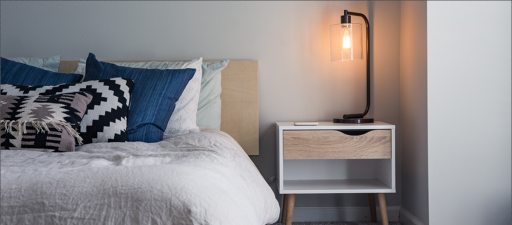 hotel room bed and side table with lamp